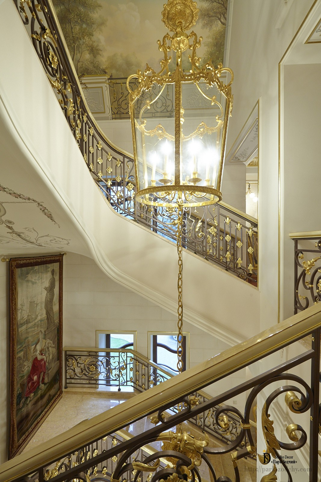 Staircase in a country mansion with paintings and gilding