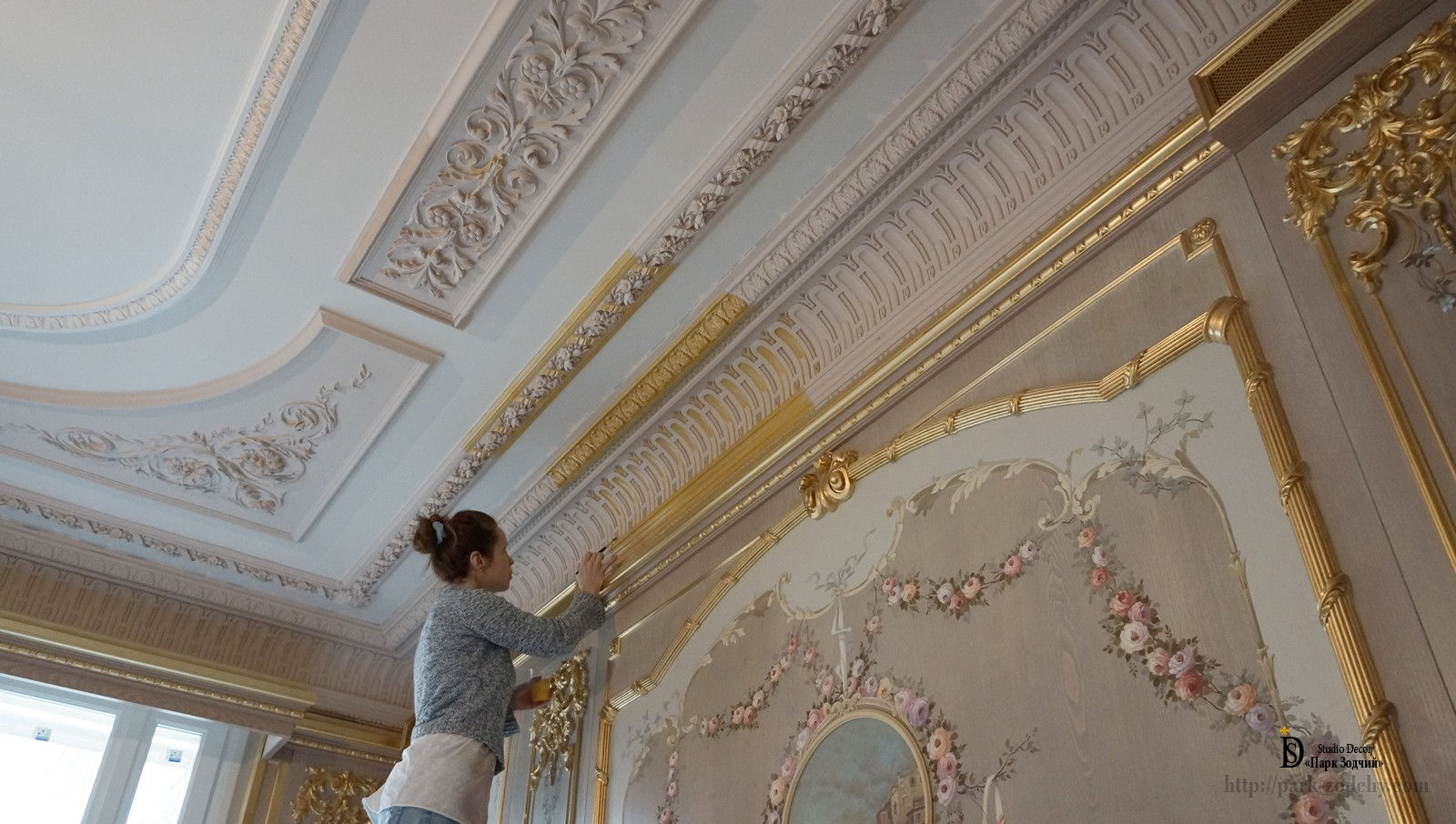 The gilding of the cornice over wooden panel