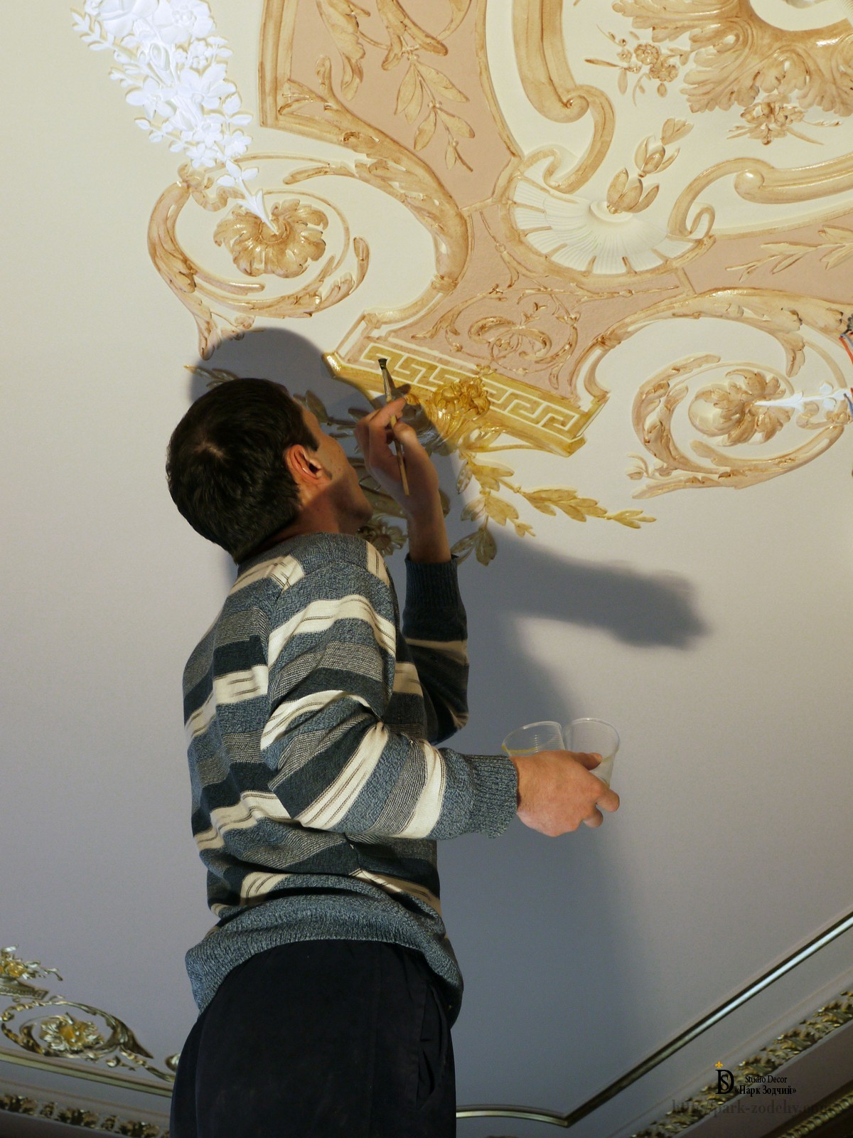 Applying nail Polish in front of the gilt stucco outlet