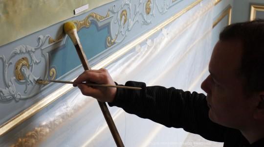 Художник выполняет роспись на стене